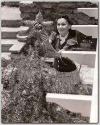 On the grounds of her lovely California home, Maureen decorates her 1939 Christmas tree.
